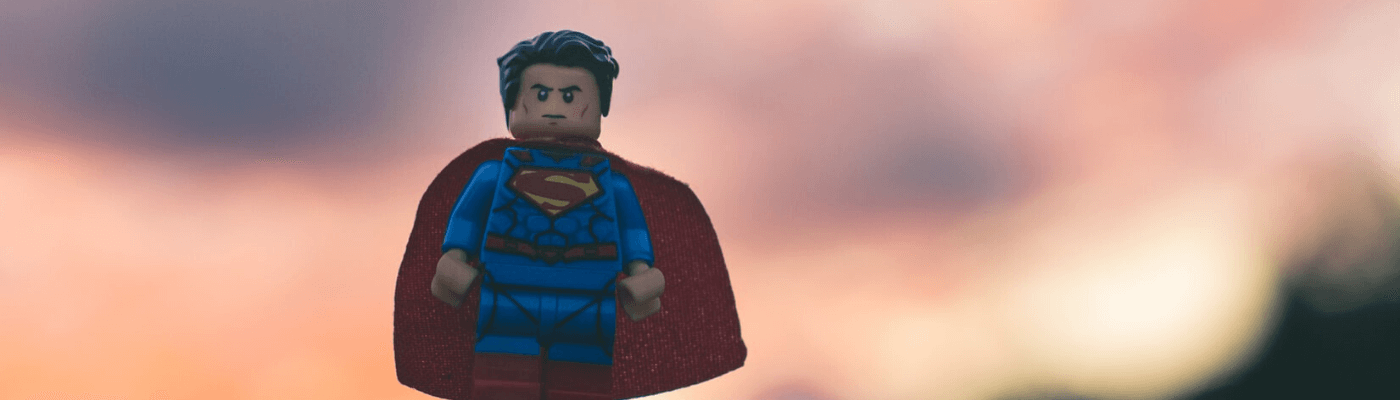 An image of a superman doll against a sunset background