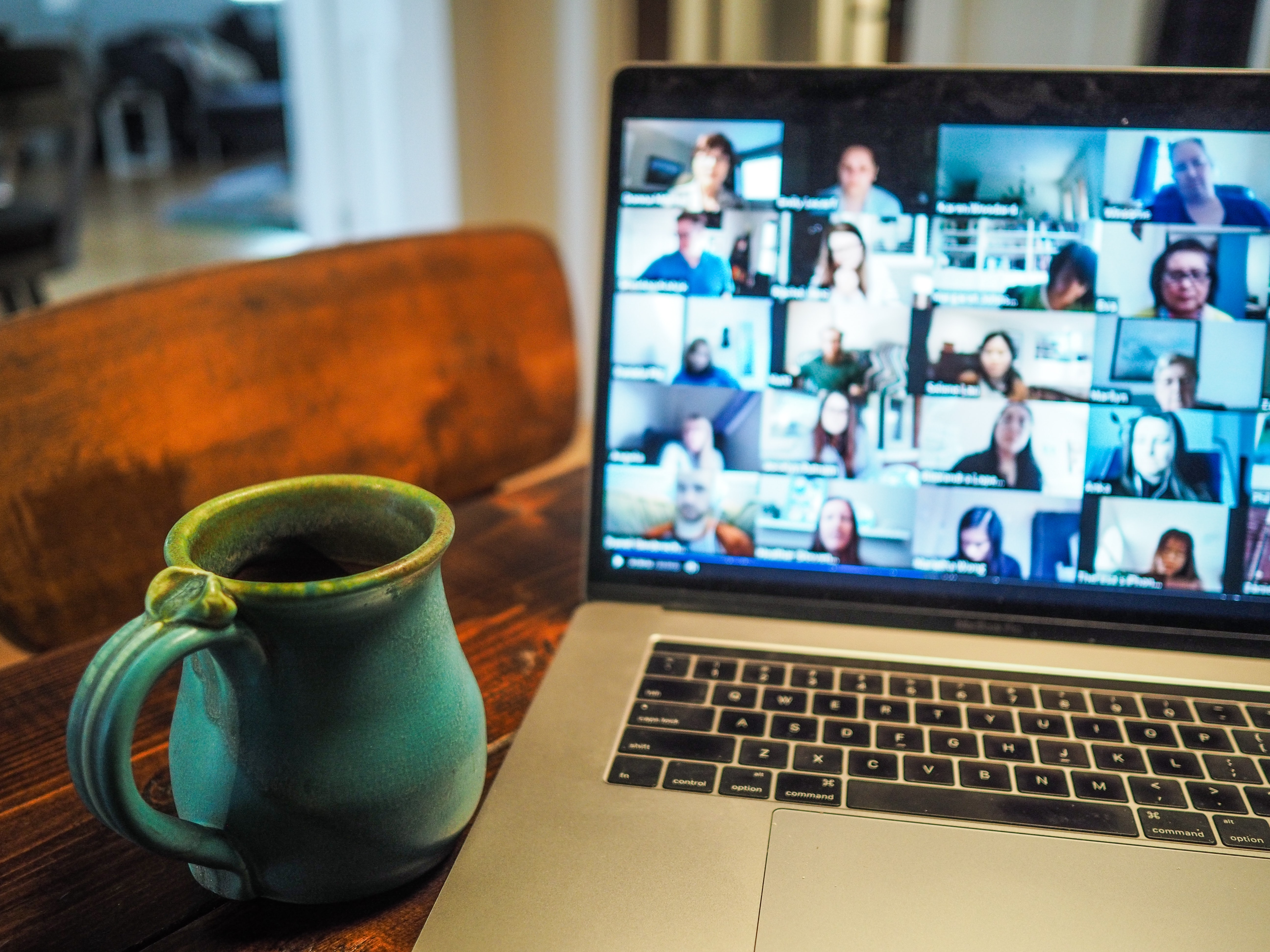 A laptop showing employees in a virtual meeting